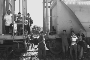 """Central Americans wait for the freight train they call """"La Bestia"""" (The Beast) to begin its trip north from Tenosique, Mexico, to Texas. Photo by Jordan Weiner."""