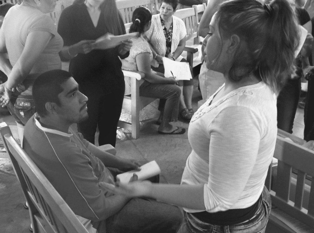 Juan Zamora (left), who came from Mexico at age fourteen, talks with volunteer Angela Reyes about his application for Deferred Action for Childhood Arrivals (DACA). Photo by Denise Holley.