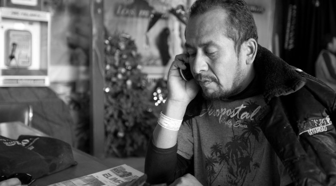 After being forcibly repatriated to Mexico, a man uses the No More Deaths phone service to contact family members. Photo by Bob Torres.