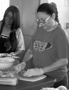 "Rosa Robles Loreto (right), with Ana Bitsoie, chops vegetables for Cross Streets Community, a program of free meals and showers at Southside Presbyterian Church. During her year living at the church, Robles Loreto has come to know homeless people she used to see in the streets, she said. ""Now, for me, these people have a face."" Photo by Denise Holley."