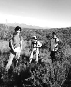 NMD volunteers Tayeb Zaidi, Lois Martin, and Ryan Tombleson walk a trail west of Tucson, Arizona in August to leave jugs of water where thirsty migrants may find them. Photo by Jim Marx.