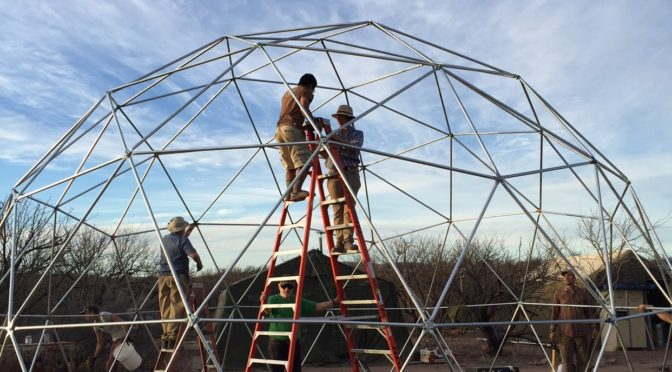 No More Deaths volunteers Max Danielewicz (left) and Catherine Gaffney fasten rivets on a 24-foot dome at Byrd Camp near Arivaca, Arizona on February 21. Pacific Domes of Ashland, Oregon heard about the work of NMD and donated the dome, said Easton Smith, who served as volunteer coordinator for summer 2015. Once it is covered, the dome will replace the aging medical tent as a treatment area for migrant guests. Photo: Lois Martin.